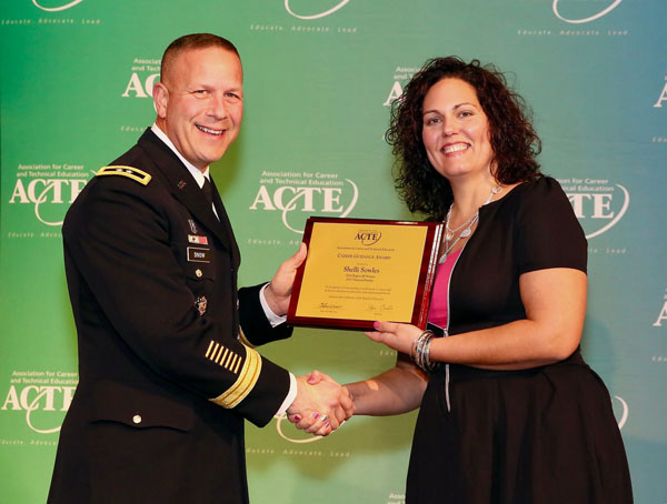 Picture of Shelli Sowles from century College, MN, recieving an award plaque.